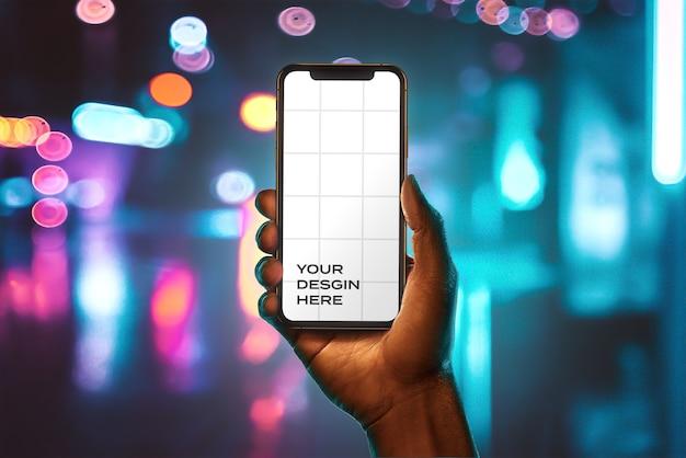Mão mão segurando nova maquete de smartphone com bokeh Psd Premium