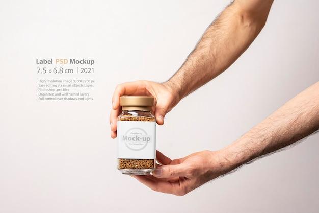 Mão masculina segurando uma maquete de frasco de vidro de café instantâneo Psd Premium