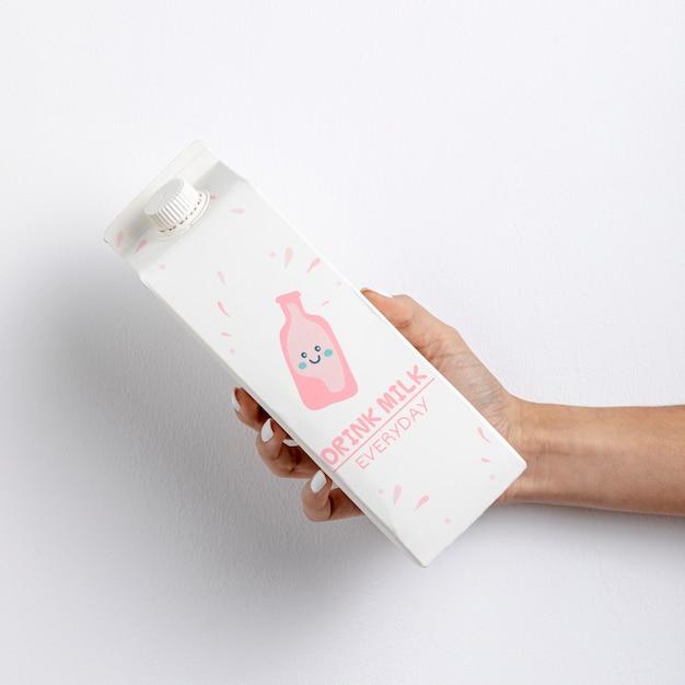 Mão segurando a caixa de leite com maquete Psd grátis