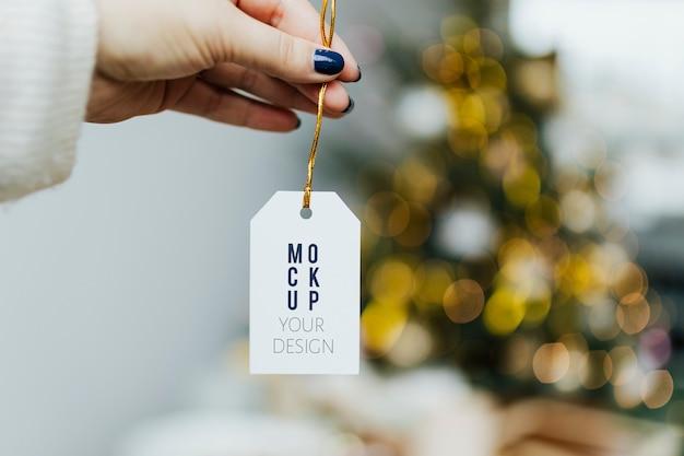 Mão segurando modelo de etiqueta de natal Psd grátis