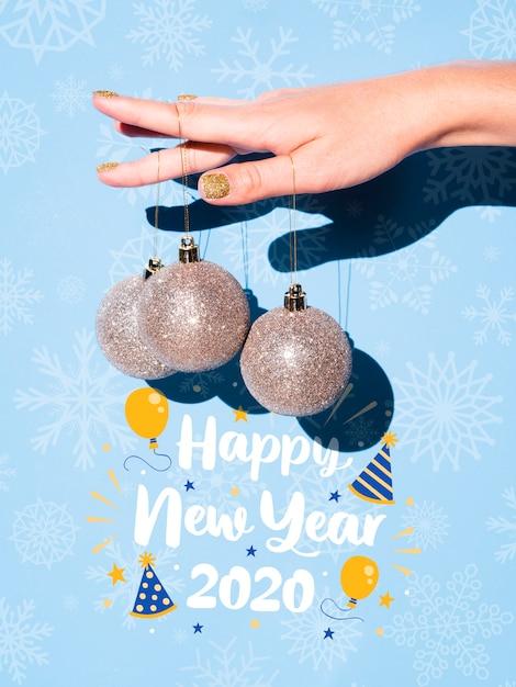 Mão segurando pendurado bolas de prata e feliz ano novo citação Psd grátis