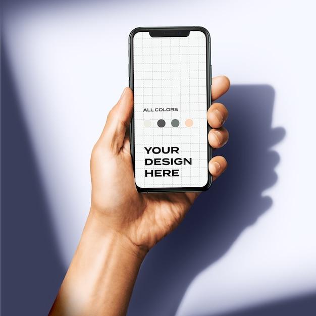 Mão segurando um novo modelo de smartphone Psd Premium
