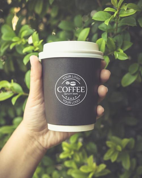 Mão segurando uma maquete de copo de papel de café Psd grátis