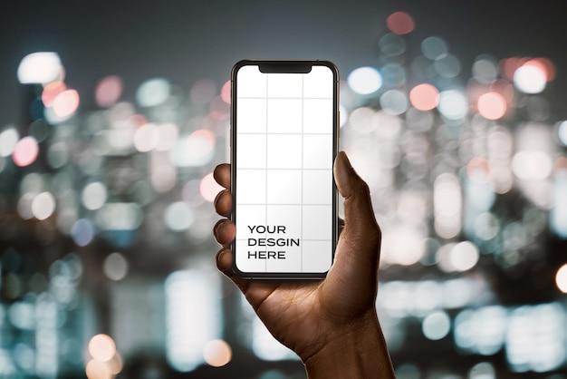 Mão segurando uma nova maquete de smartphone com bokeh Psd Premium