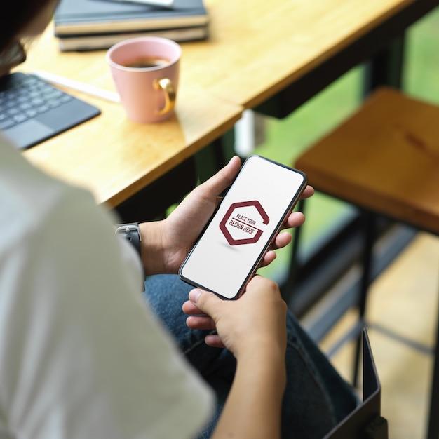 Mãos de alunos usando maquete de smartphone em cafeteria Psd Premium