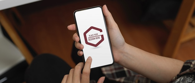 Mãos de alunos usando maquete de smartphone no escritório Psd Premium
