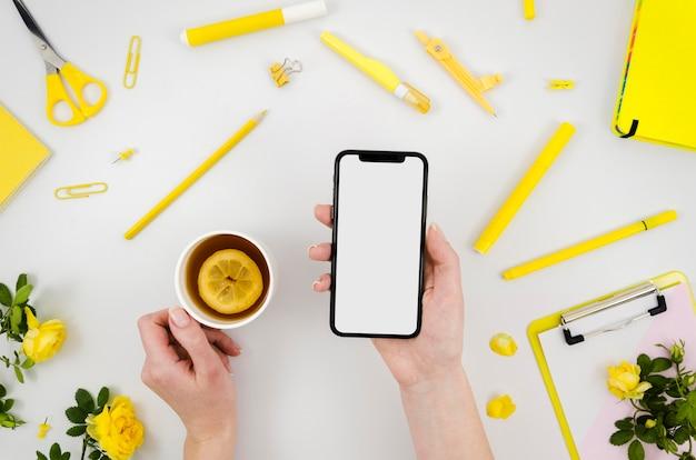 Mãos planas segurando uma maquete de smartphone com artigos de papelaria Psd grátis