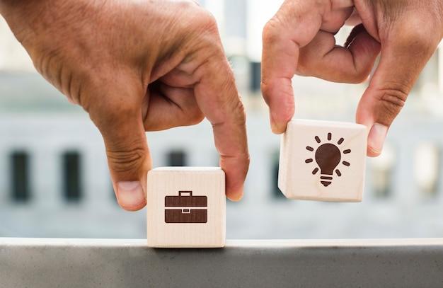 Mãos segurando dadinhos com idéias da empresa ao ar livre Psd grátis