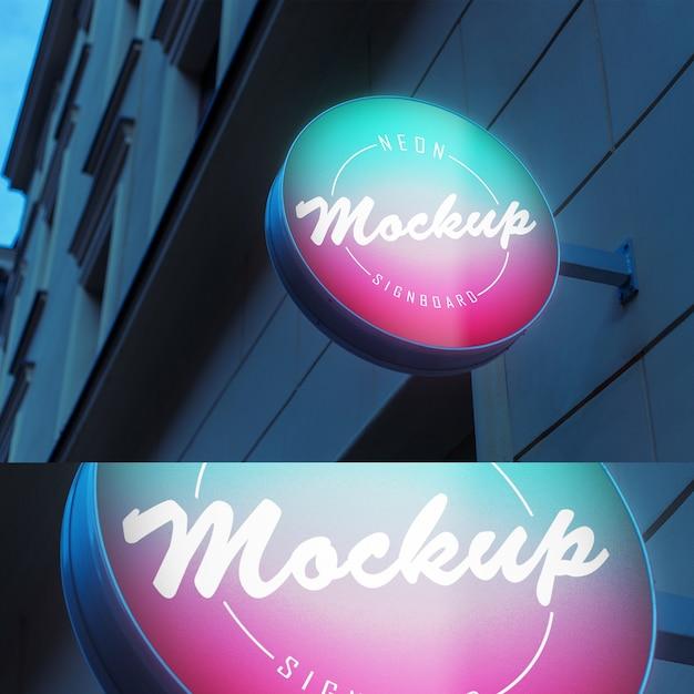 Maquete da tabuleta de néon brilhante luminescente luz com forma de círculo na construção de parede à noite Psd Premium