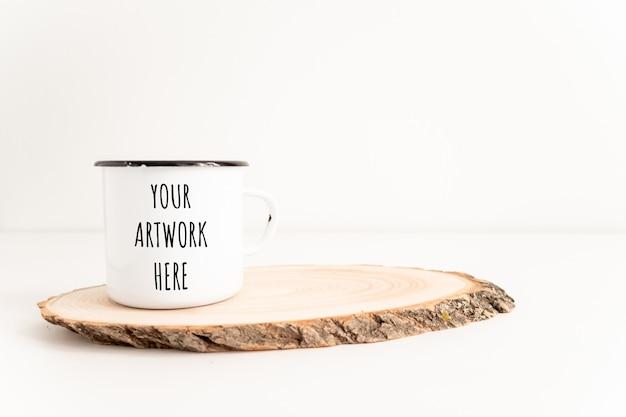 Maquete de caneca de esmalte com seção de árvore de corte de madeira na mesa branca. projeto boho de copo de estanho Psd Premium