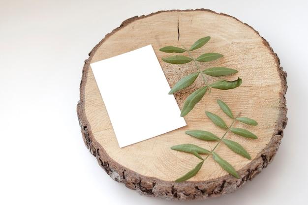 Maquete de cartão de casamento em um espeto de madeira com folhas de pistache Psd Premium