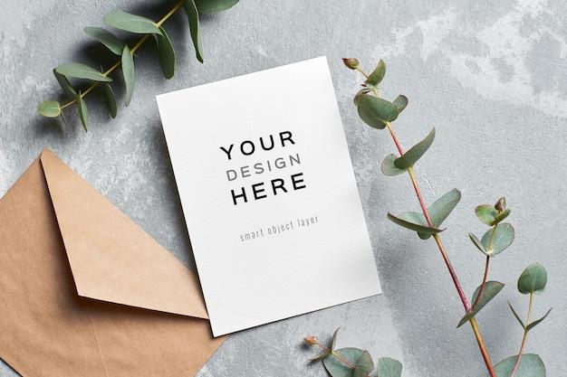 Maquete de cartão de convite de casamento com envelope e galho de eucalipto Psd Premium