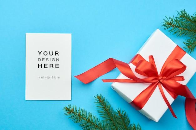 Maquete de cartão de felicitações com caixa de presente de natal e galhos de pinheiro Psd Premium