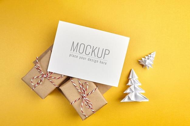 Maquete de cartão de felicitações com caixas de presente e árvores de natal de papel com fundo dourado Psd Premium