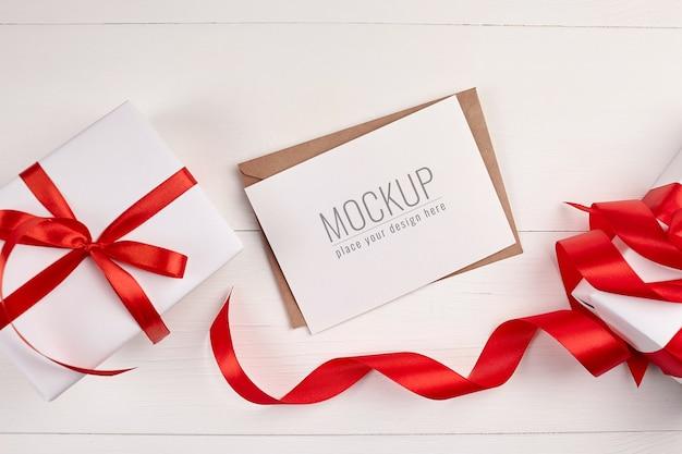 Maquete de cartão de felicitações com caixas de presente e fita vermelha Psd Premium