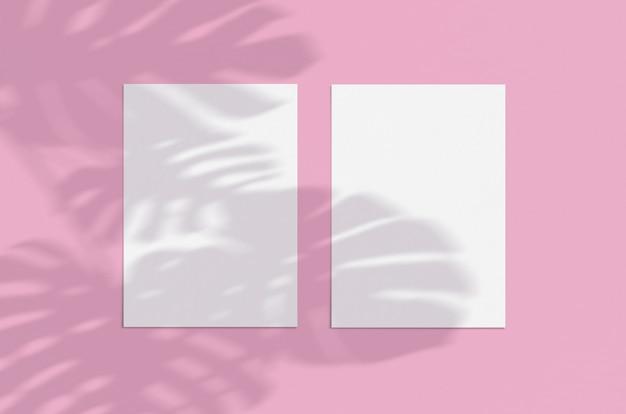 Maquete de cartão de folha de papel vertical branco em branco na rosa com monstera deixa a sobreposição de sombra. cartão moderno e elegante mock up Psd Premium