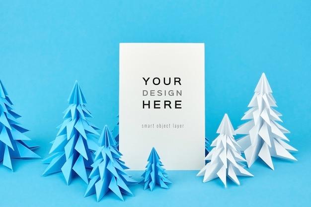 Maquete de cartão de natal com pinheiros de papel azul e branco Psd Premium