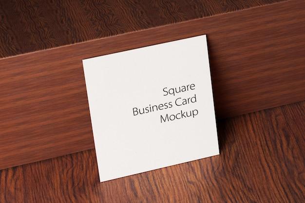 Maquete de cartão de papel quadrado na mesa de madeira Psd Premium