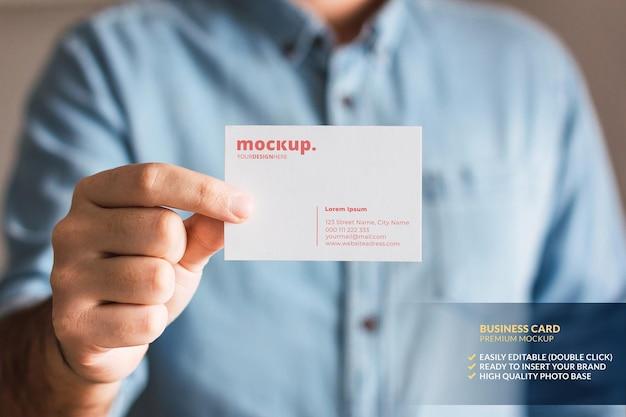 Maquete de cartão de visita segura pela mão de um homem Psd Premium