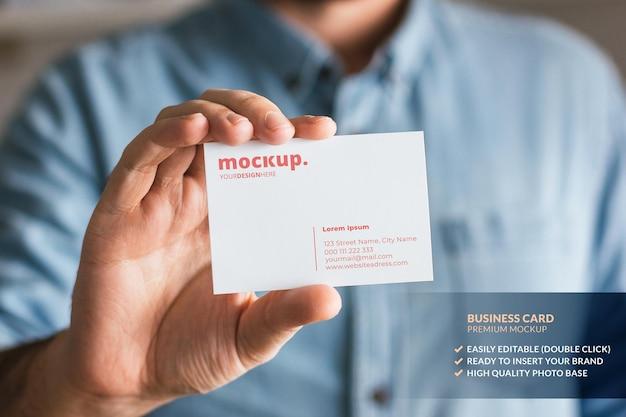 Maquete de cartão de visita segurado por um homem na mão Psd Premium