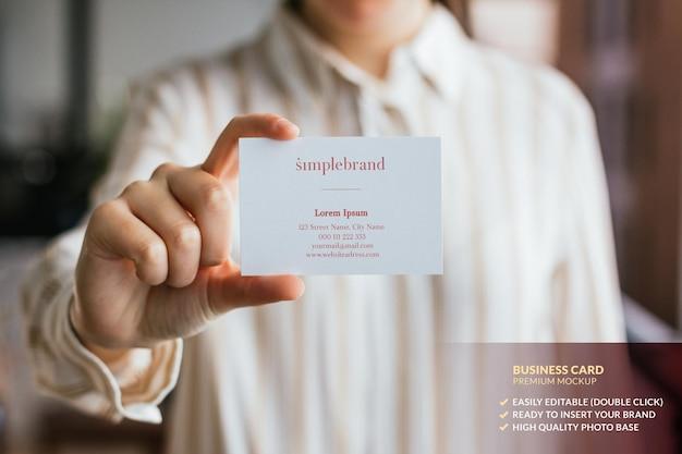 Maquete de cartão de visita segurado por uma mão de mulher Psd Premium