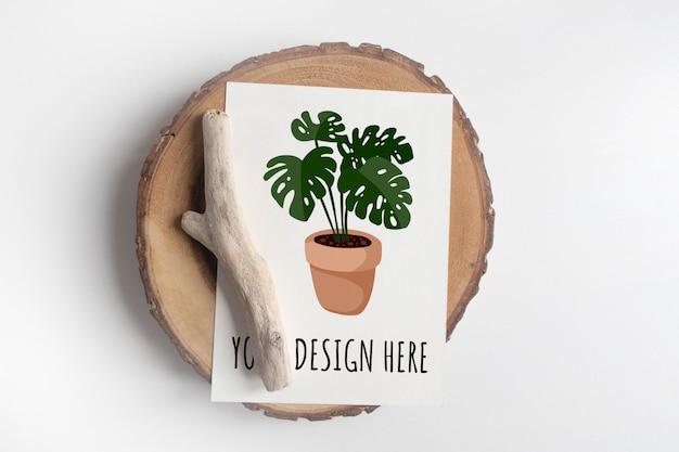 Maquete de cartão postal na seção de árvore de corte de madeira na mesa branca. boho design de cartão postal na mesa branca Psd Premium