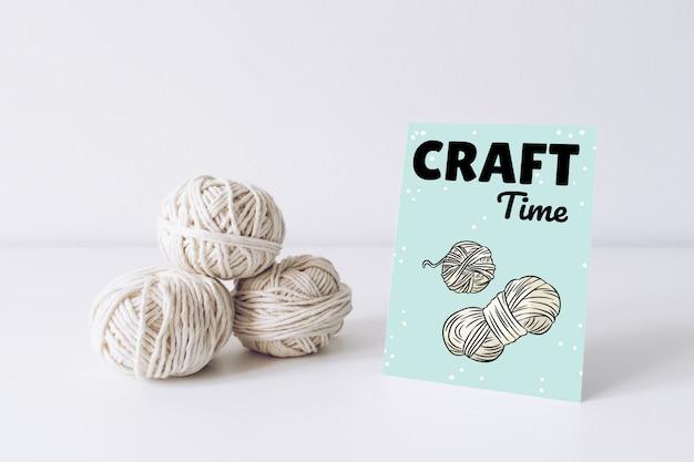 Maquete de cartão postal vertical com fio branco sobre uma mesa branca. linhas de imagem de boho de lã de corda. Psd Premium