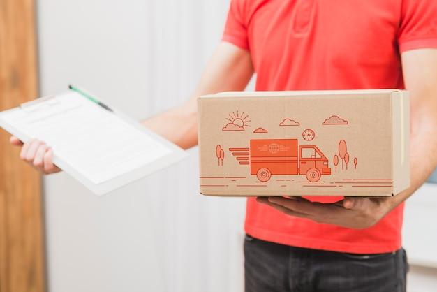 Maquete de entrega com homem segurando a caixa e a área de transferência Psd grátis