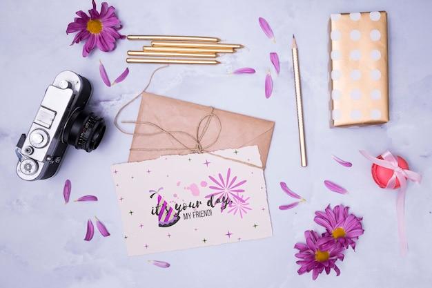 Maquete de feliz aniversário com envelopes amarrados e flores Psd grátis