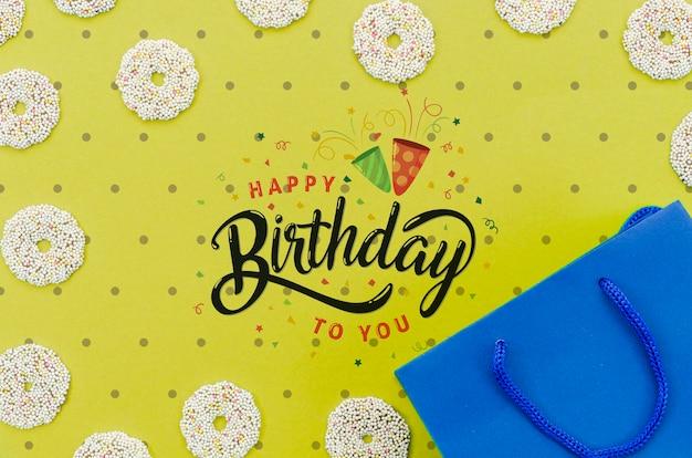 Maquete de feliz aniversário com sacola de compras e donuts Psd grátis