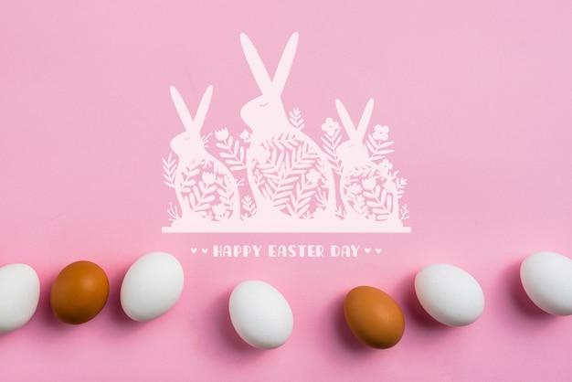 Maquete de fundo rosa com ovos de páscoa e coelhinhos Psd grátis