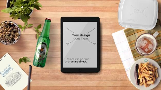 Maquete de garrafa de cerveja e tablet tablet fundo de madeira Psd Premium