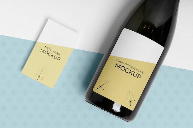 Maquete de garrafa de champanhe com cartão de visita com o mesmo design Psd grátis