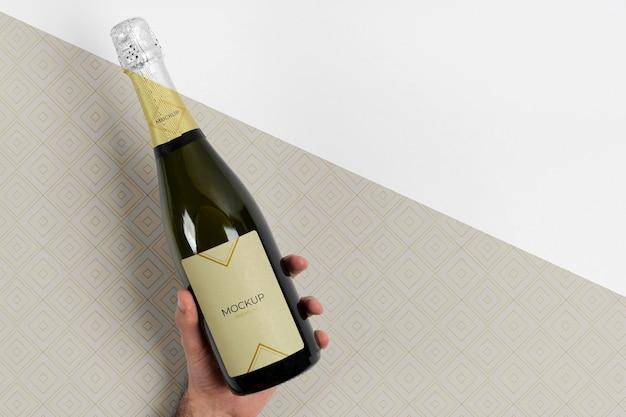 Maquete de garrafa de champanhe em mãos Psd grátis