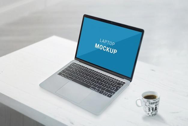 Maquete de laptop na mesa de escritório branco. xícara de café ao lado Psd Premium