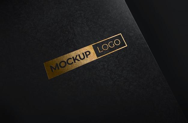 Maquete de logotipo de folha de ouro com fundo de papel preto Psd Premium
