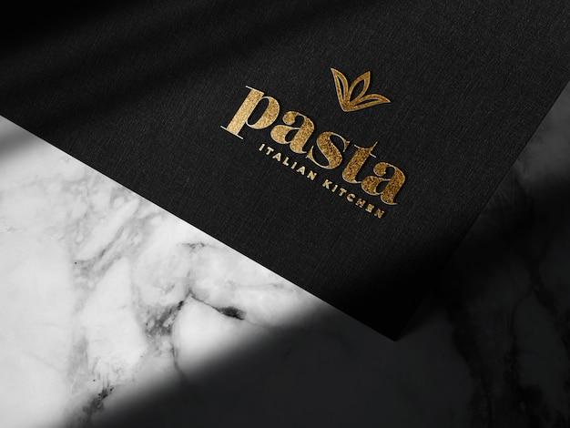 Maquete de logotipo de ouro em relevo de luxo em papel preto Psd grátis