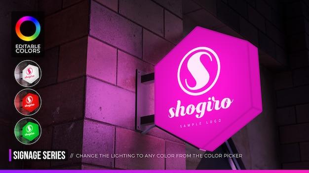 Maquete de logotipo de sinal hexágono na fachada ou loja com iluminação diurna e noturna Psd Premium