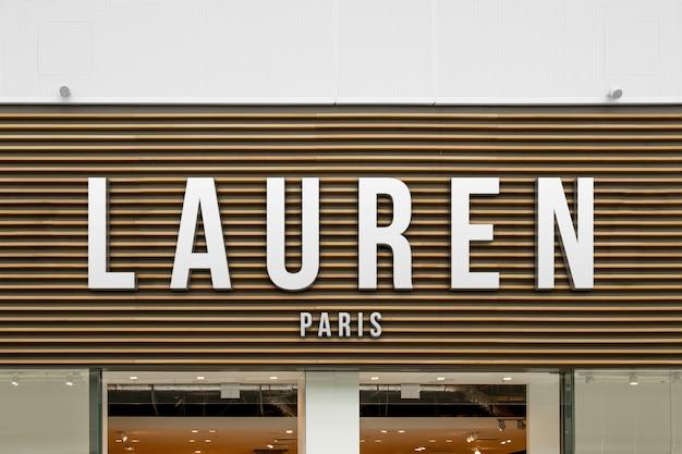 Maquete de moda elegante branco exclusivo logotipo 3d sinal na fachada da loja de madeira ou entrada da montra Psd Premium
