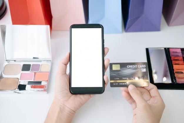 Maquete de mulher bonita, segurando o cartão de crédito, compras on-line com smartphone em sites on-line Psd Premium