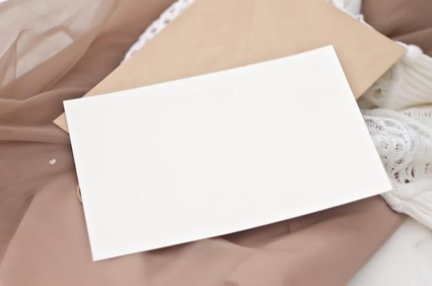 Maquete de papelaria em estilo vintage. cartão do modelo no envelope ofício para seu projeto, convites, saudações, letras ou ilustrações. as suaves cores bege e brancas. camada inteligente psd Psd Premium