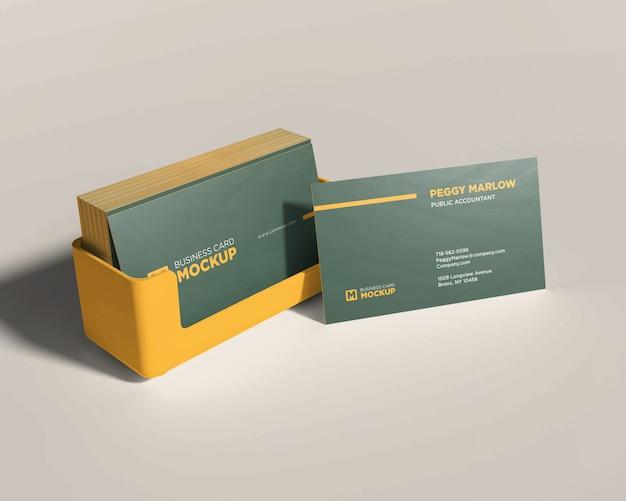 Maquete de papelaria empilhado cartão de visita em caixa amarela Psd Premium
