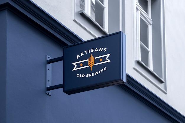 Maquete de rua ao ar livre urbano preto retangular 3d logo sinal pendurado na fachada Psd Premium