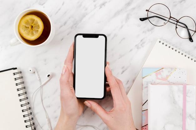 Maquete de smartphone de vista superior com chá e copos Psd Premium