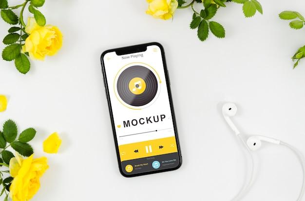 Maquete de smartphone plana com flores e fones de ouvido Psd grátis