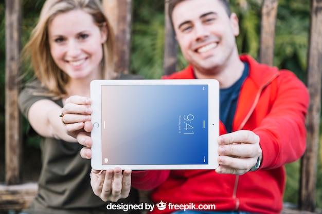 Maquete de tablet com casal ao ar livre Psd grátis