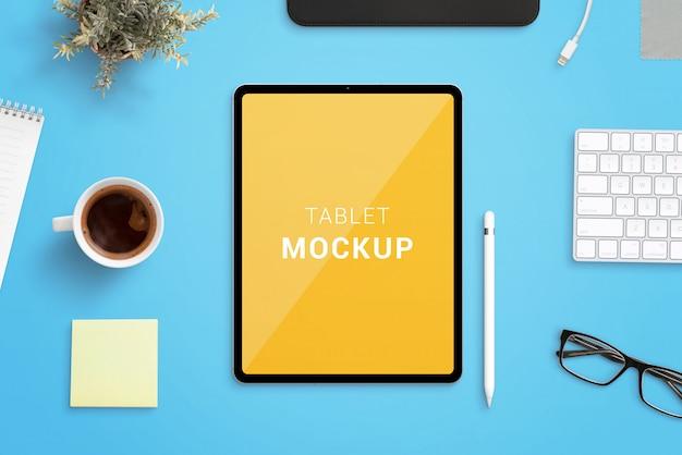 Maquete de tablet na mesa de escritório, rodeada por caneta, xícara de café, teclado, planta, almofada e óculos. tablet moderno com bordas finas e redondas Psd Premium