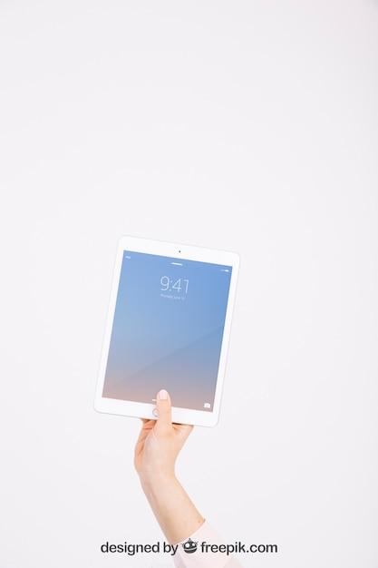 Maquete de tecnologia com mão mostrando o tablet Psd grátis