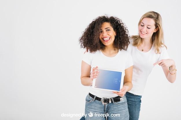Maquete de tecnologia com mulheres mostrando tablet Psd grátis