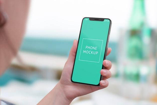 Maquete de telefone móvel na mão da mulher. vista acima do ombro. telefone inteligente moderno com bordas redondas Psd Premium